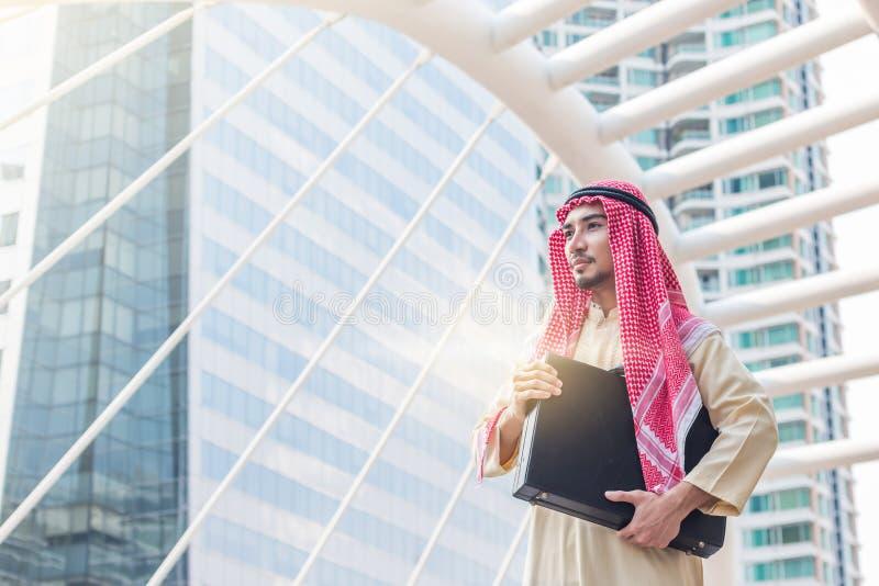 拿着公文包和站立在有承诺的街市的年轻阿拉伯商人画象对与大厦的成功 免版税库存照片
