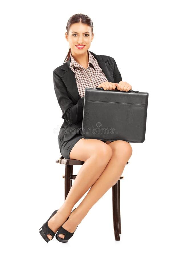 拿着公文包和等待在椅子的女实业家 免版税库存图片