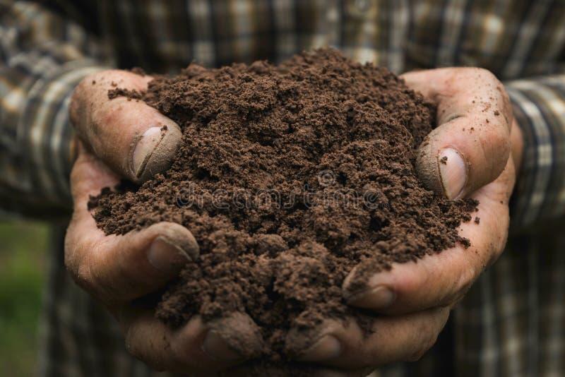 拿着农业的人的特写镜头手丰盈土壤或 免版税库存图片