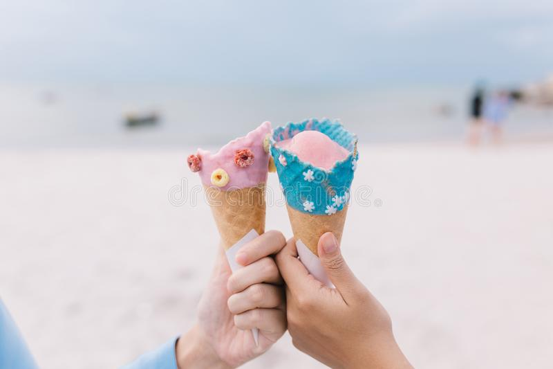 拿着冰淇淋锥体的两名手青少年妇女在夏天在海滩和海 免版税图库摄影