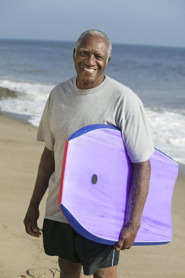 拿着冲浪板的老人 库存照片