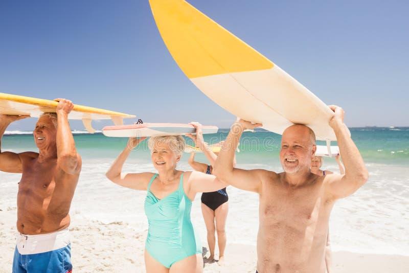 拿着冲浪板的资深朋友 免版税图库摄影