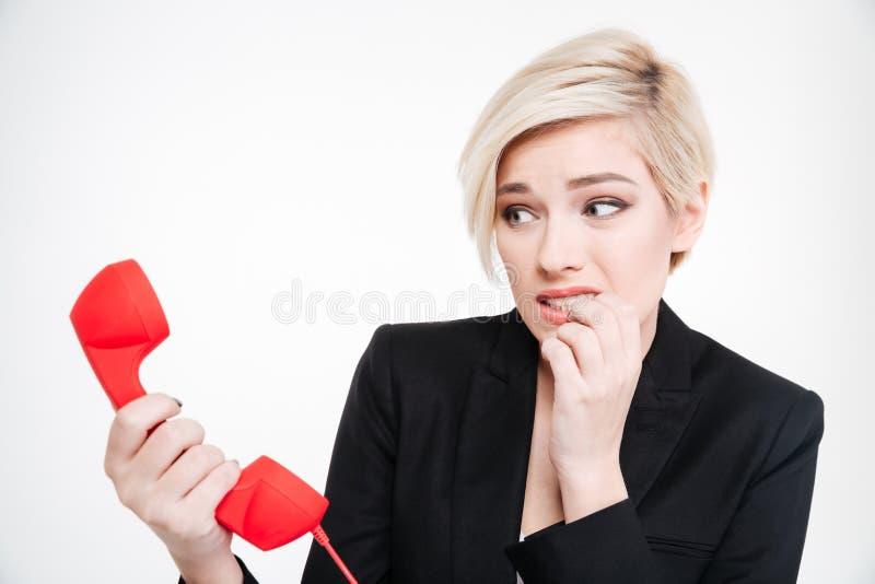 拿着减速火箭的电话管的害怕女实业家 库存图片