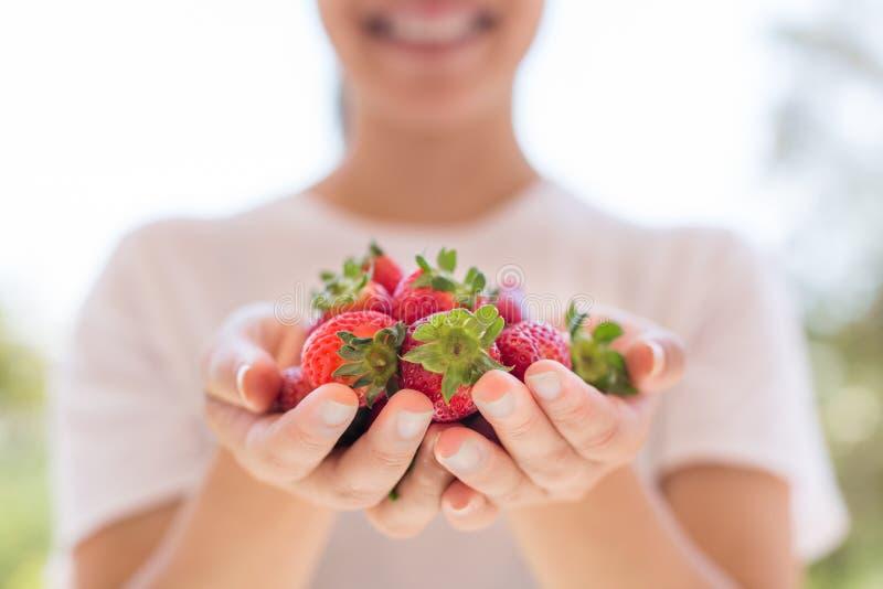 拿着几个草莓的健康妇女在庭院里 免版税库存图片