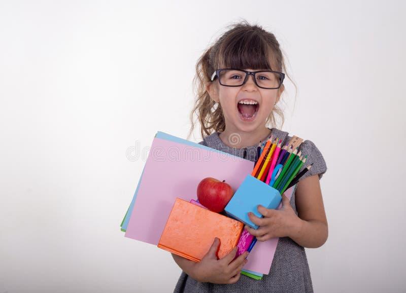 拿着凹道和油漆供应的镜片的聪明的孩子 哄骗愉快回到学校 免版税图库摄影