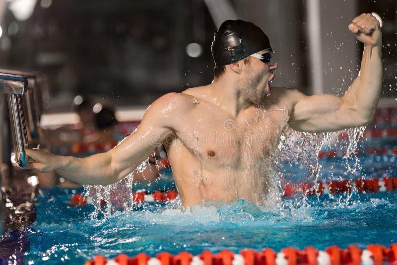 拿着出发台的愉快的男性游泳者 图库摄影