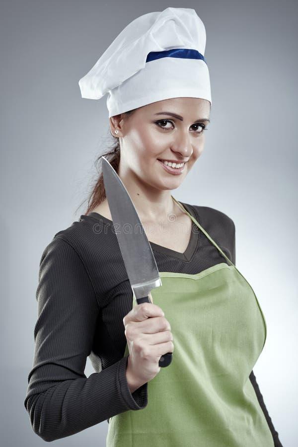 拿着刀子的妇女厨师 库存照片