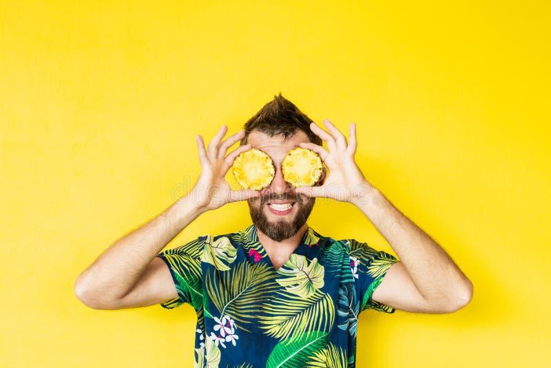 拿着切片在他的眼睛前面的菠萝的年轻有胡子的人,笑 库存照片