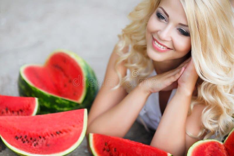 拿着切片成熟西瓜的美丽的少妇 免版税图库摄影