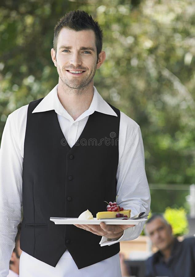 拿着切片饼的英俊的侍者在咖啡馆 免版税库存图片