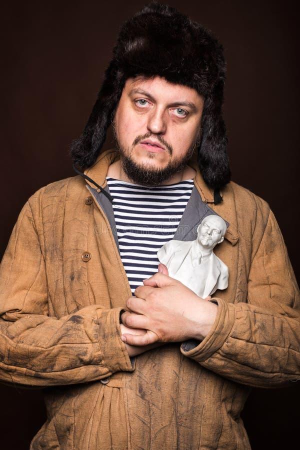 拿着列宁雕塑的哀伤的俄国人 免版税图库摄影
