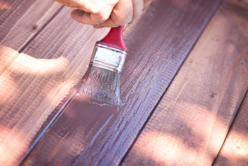 拿着刷子和绘木头的人的手 免版税库存照片