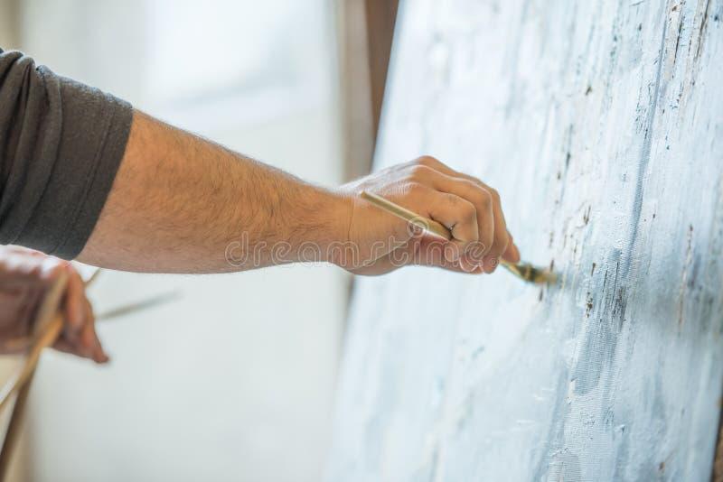 拿着刷子和绘在帆布的一个人的手 免版税图库摄影