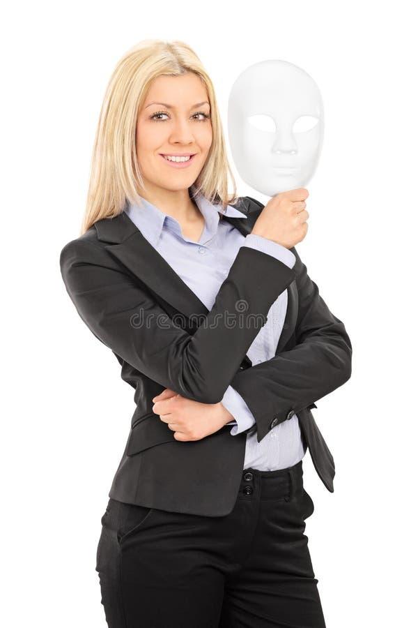 拿着剧院面具的女实业家 免版税库存图片