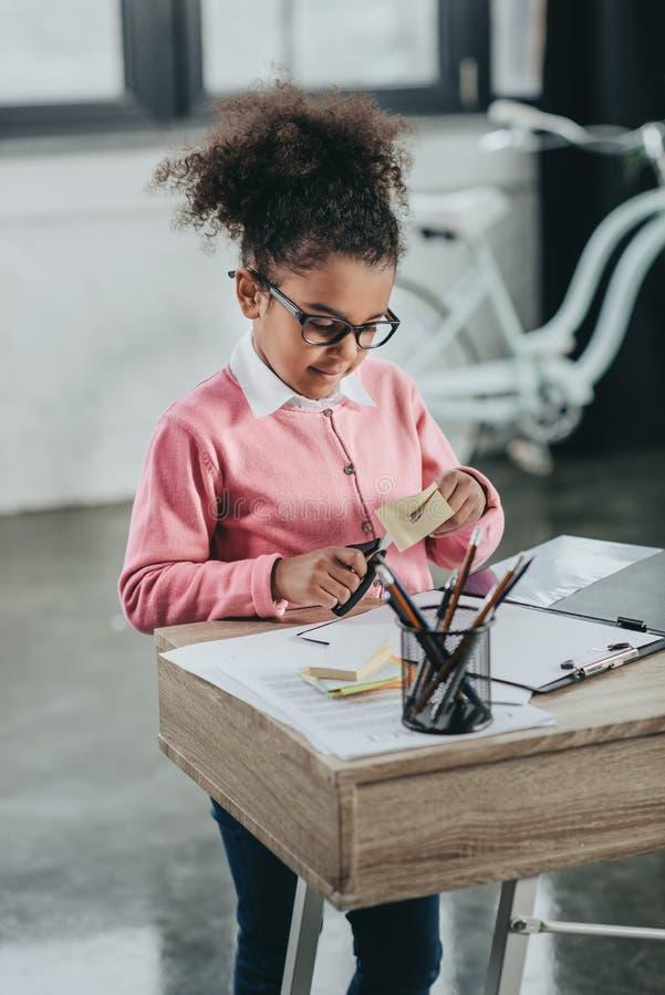 拿着剪刀和切开纸的镜片的小女孩在办公室桌上 免版税库存照片