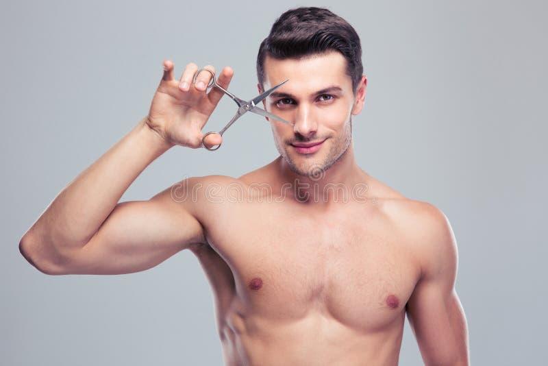 拿着剪刀的年轻英俊的人 免版税库存照片