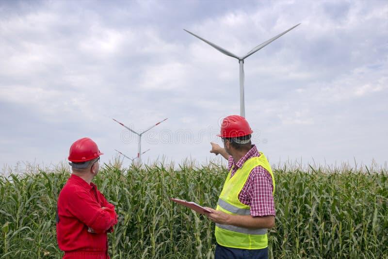 拿着剪贴板的工程师站立与工友在风力场 免版税库存照片