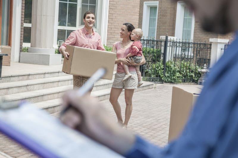 拿着剪贴板和发货票,家庭的搬家工人在背景中 免版税库存图片