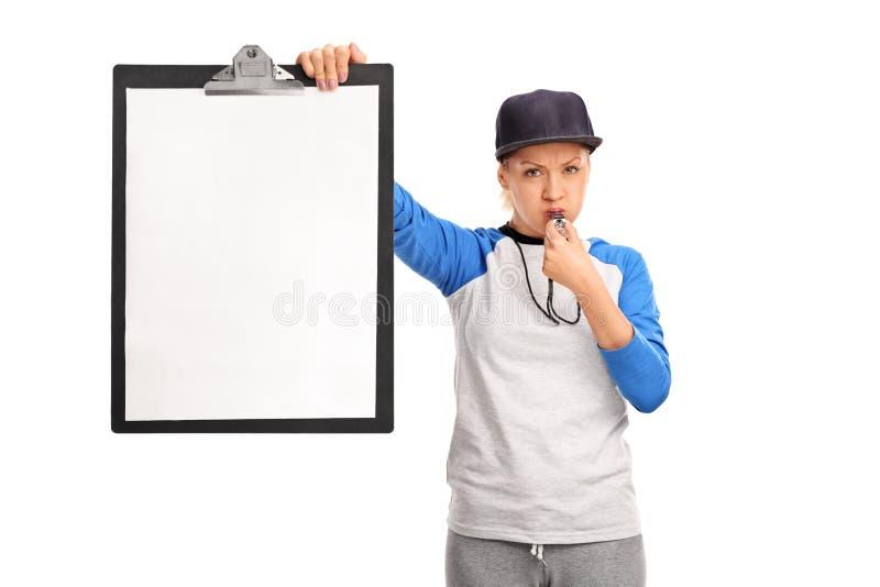 拿着剪贴板和吹口哨的女性教练 库存照片