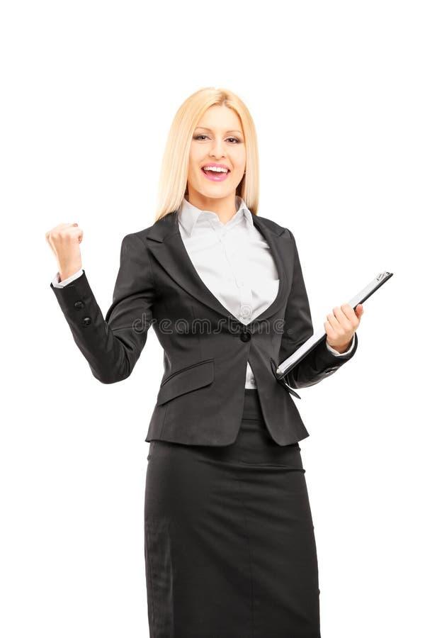 拿着剪贴板和打手势happ的年轻职业妇女 库存图片