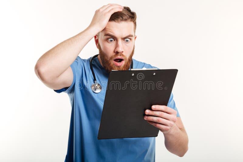 拿着剪贴板和抓他的头的惊奇的年轻医生 库存照片