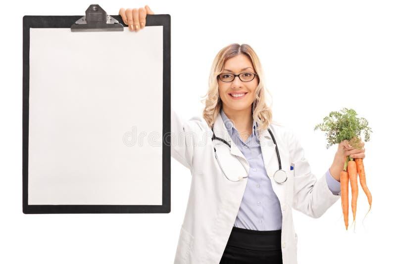 拿着剪贴板和红萝卜的女性医生 免版税库存图片