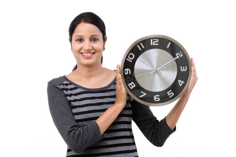 拿着办公室时钟的快乐的少妇 免版税图库摄影