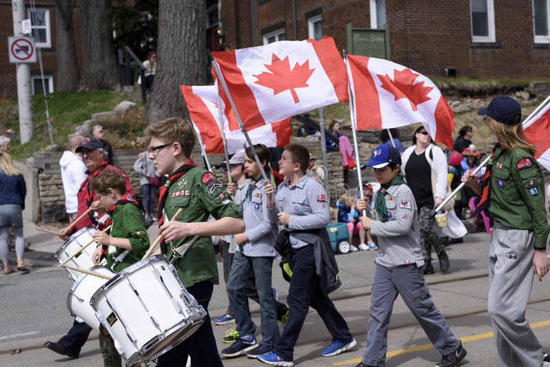 拿着加拿大旗子的侦察员加拿大的成员沿Quee前进 库存照片