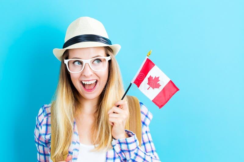 拿着加拿大旗子的年轻旅行的妇女 免版税库存图片