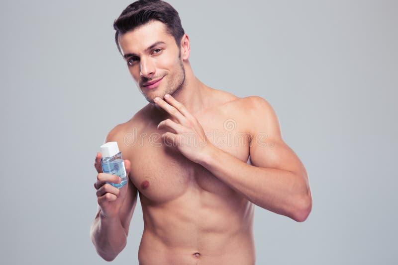 拿着化妆水的英俊的年轻人 免版税库存图片