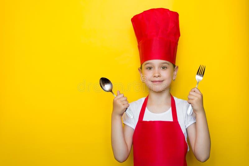 拿着匙子和叉子的一位红色厨师的衣服的微笑的女孩,邀请到晚餐,在与拷贝空间的黄色背景 免版税图库摄影