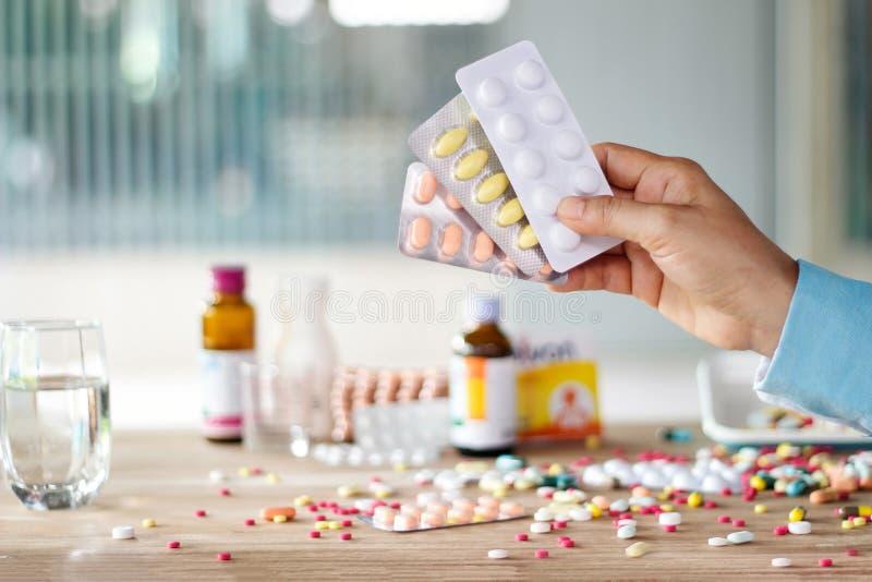 拿着医学与五颜六色的药物的手药片组装传播了  库存照片