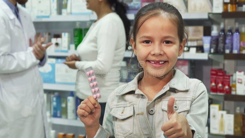 拿着医学和显示赞许的小女孩 图库摄影