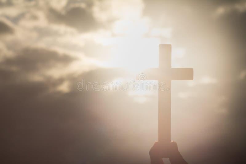 拿着十字架的人的手,背景是日出 浓缩 库存照片