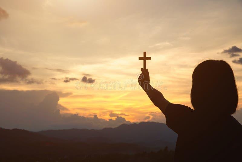 拿着十字架的女孩的手在日出,圣餐疗法保佑帮助葡萄生根的宽容复活节被借的头脑的上帝祈祷 祷告 库存照片