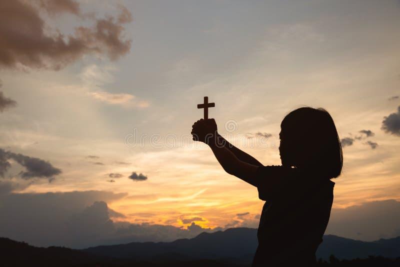 拿着十字架的女孩的手在日出 对上帝基督徒宗教概念背景的祷告 免版税库存照片