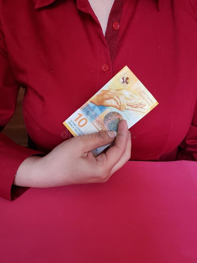 拿着十法郎的瑞士钞票女实业家的手 免版税库存图片