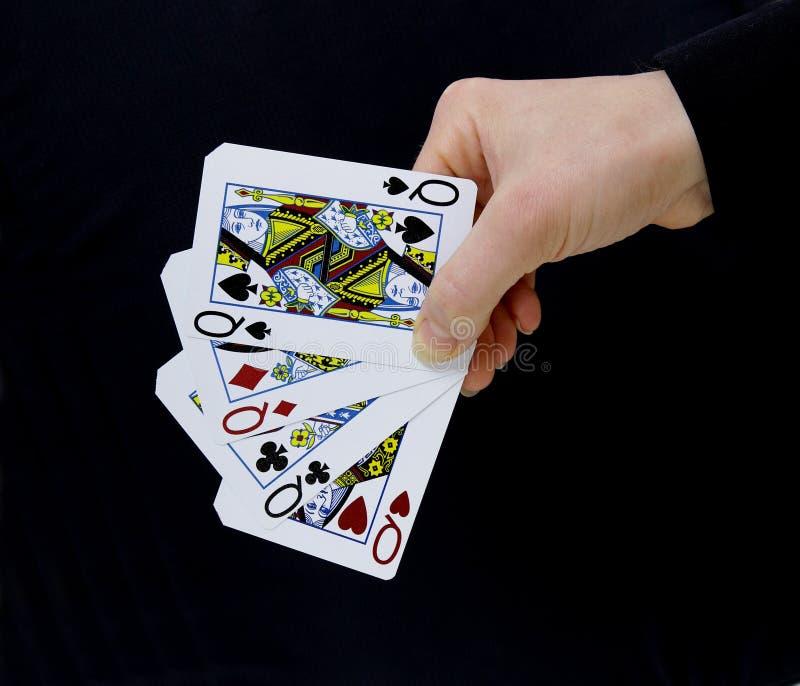 拿着卡片女王/王后四张相同的牌的副主持人球员 库存图片