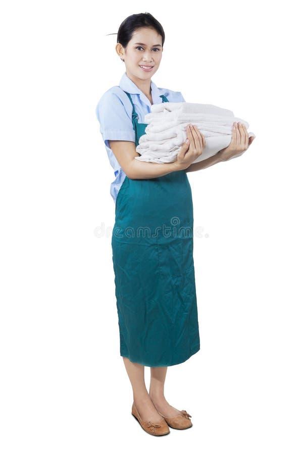 拿着卧具和毛巾的年轻佣人 图库摄影