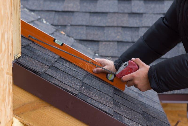 拿着卷尺和水平的盖屋顶的人 图库摄影