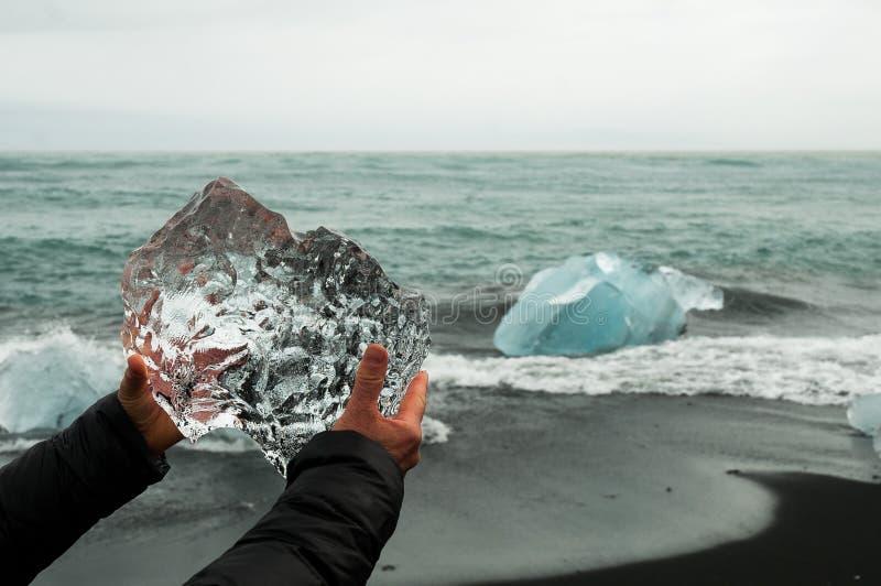 拿着原始冰川冰的块手 图库摄影