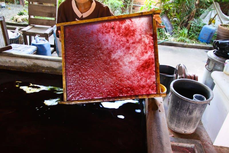 拿着原料的妇女被固定在纸伞的一个框架在Bo唱了村庄,清迈,泰国 免版税库存照片