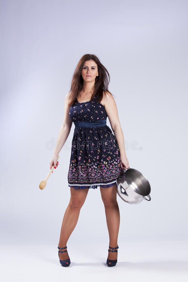 拿着厨房器物的美丽的妇女 免版税库存照片