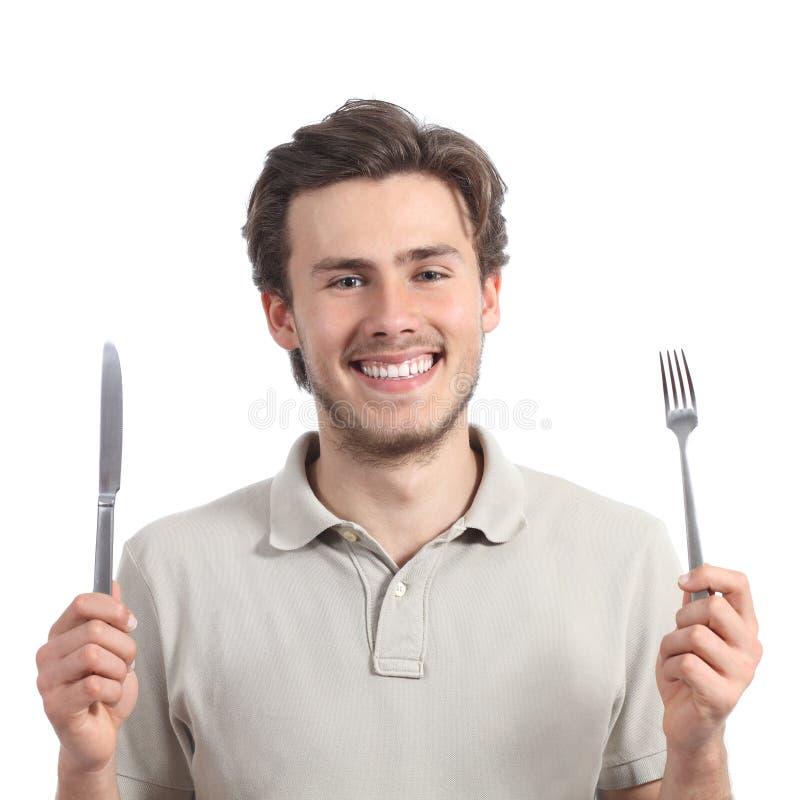 拿着叉子和刀子的年轻愉快的人 免版税图库摄影