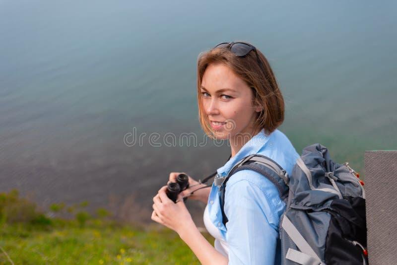 拿着双筒望远镜和摆在为照相机的一名年轻白肤金发的妇女 休闲和远足的概念 库存照片