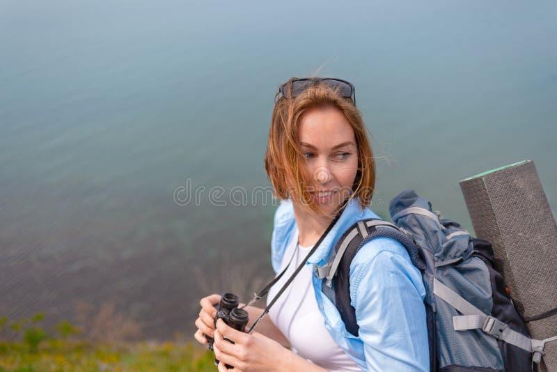 拿着双筒望远镜和摆在为照相机的年轻女人 休闲和远足的概念 免版税库存图片