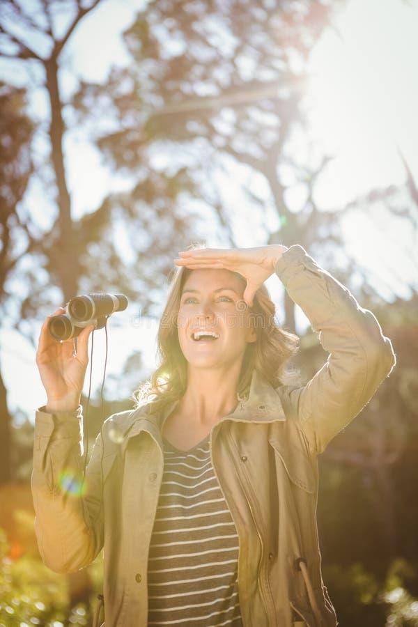 拿着双筒望远镜的微笑的妇女 免版税库存照片