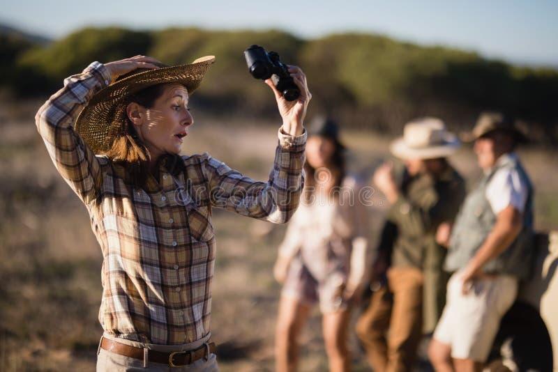 拿着双筒望远镜的震惊妇女在徒步旅行队假期时 免版税图库摄影