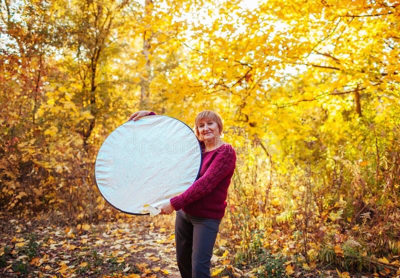 拿着反射器的中年妇女协助 免版税图库摄影