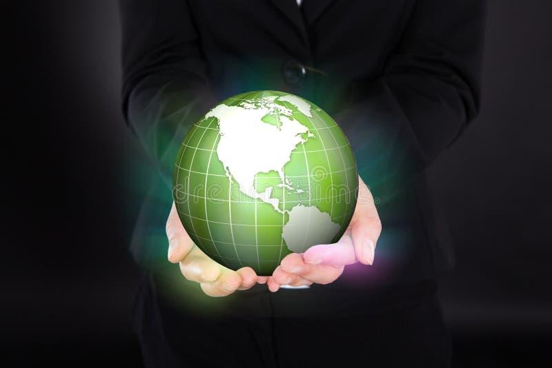 拿着发光的绿色地球的女实业家 免版税库存图片